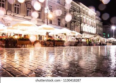 Nachtlandschaft mit Blick auf ein Café in Europa in der Altstadt, Aufnahme im Regen, ein Foto mit Bokeh-Elementen.