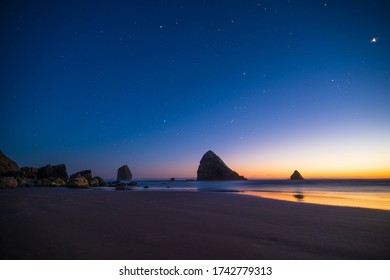 Night landscape of pacific ocean beach in USA, cliffs, and night stars. Beautiful sunset