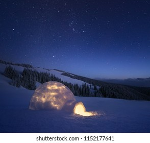 Night landscape with a snow igloo with light. Extreme house. Winter in the mountains. Sky with the stars