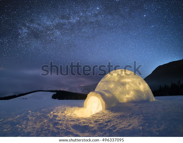 Night landscape with a snow igloo with light. Extreme house. Winter in the mountains. Sky with the stars and the Milky Way