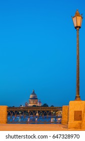 Night landscape in St. Petersburg with a view of the granite parapet, high lamp, the Neva River and St. Isaac's Cathedral