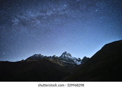 Night landscape. Starry sky with the Milky Way over the mountains. Mount Ushba in the light of the rising moon. Main Caucasian ridge. Zemo Svaneti, Georgia