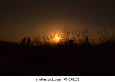 Night landscape with sunset sunlight and people walking on the beach dune