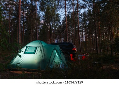Night landscape with a tent in the forest near lake. The light from the lantern in a tent. Car and portable table and chairs, green tourist tent. Romantic evening with a tent at night.