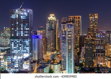 Night light of Bangkok. Panoramic and perspective view light blue background of glass high rise building skyscraper commercial of future. Business concept of success industry tech architecture