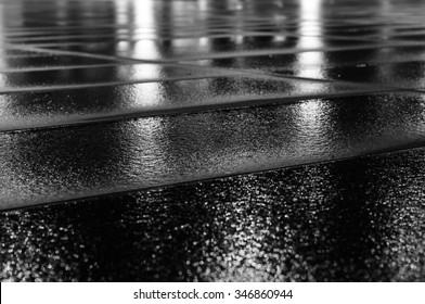 Night light reflection on wet paving slab after rain. Black and white image with selective focus