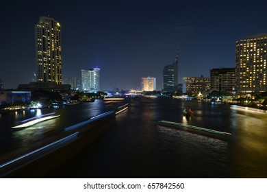 Night light at river in Bangkok city with speed light on the boat in river