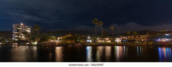 Night lights reflecting in Hawaii Kai Marina, near Honolulu, Hawaii, on the Hawaiian island of Oahu - water reflections of Christmas light decorations and Mount Terrace residential condominium