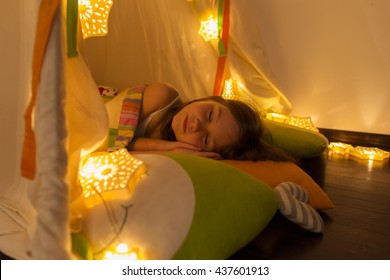 The night. little girl sleeping in a tent. Houses, bedside lamp