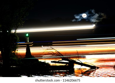 Night long exposure composite of a barge passing on the Mississippi river at Midnight with a full Moon