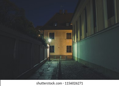 night long exposure narrow european street in old city district concept with small buildings facade and light of lantern and without people