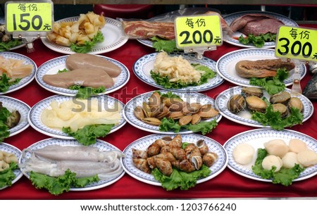 A night market food stall displays a choice of raw seafood dishes. The signs with numbers show the price per plate.