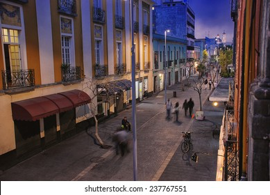 Night in Mexico City. Streets of the center with blurred people, bars, restaurants and cafes.