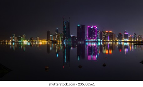 Night modern city skyline panorama with shining neon lights and reflection in the water. Manama, the Capital of Bahrain, Middle East