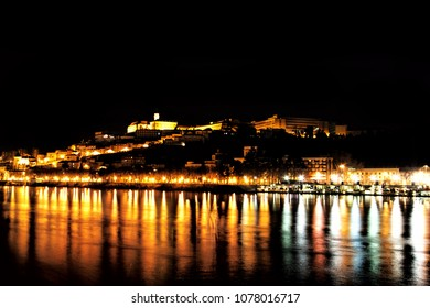 Night Mondego river colorful reflections in Coimbra, Portugal