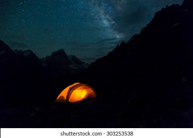 Night mountain landscape with illuminated tent. Silhouettes of mountain peaks and edges night sky with many stars and milky way on background illuminated orange tent on foreground