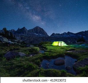 Night mountain landscape with illuminated tent. Mountain peaks and the milky way on horizon.