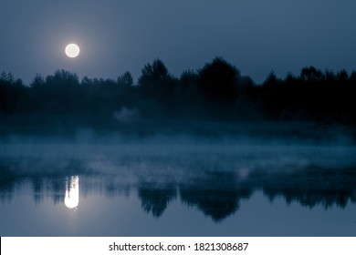 Night mystical scenery. Full moon over the foggy river and its reflection in the still water. - Shutterstock ID 1821308687
