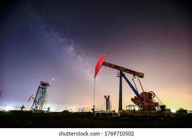 Nachts pumpen Ölpumpen unter den Sternen
