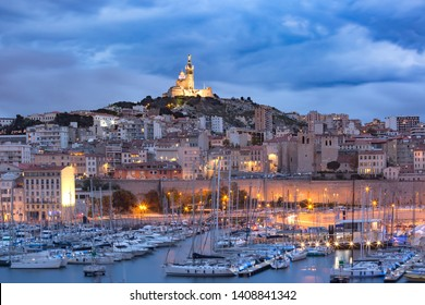 Night Old Port and the Basilica of Notre Dame de la Garde on the background, on the hill, Marseille, France