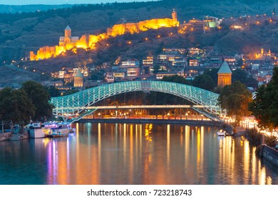Night Old Town with Narikala Fortress and illuminated Bridge of Peace across Kura river, Tbilisi, Georgia.