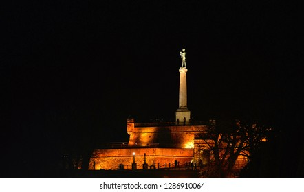 night on hill with old Kalemegdan fortress walls with column of Viktor statue and monument and people silhouettes in Belgrade, Serbia
