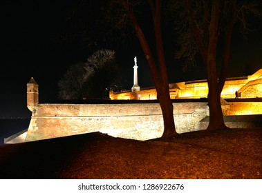 night on illuminated hill with old Kalemegdan fortress walls with column of Viktor statue and monument and silhouettes of people in Belgrade, Serbia