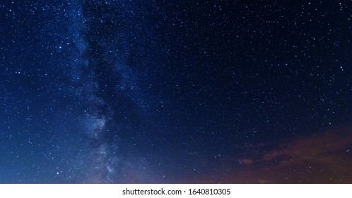 A night on the lake with a bright milky way in the sky and millions of stars glittering in the water