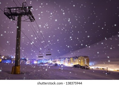 Night on ski and snowboard resort Pas de la casa, Andorra with ski lift, snowfall and illuminated village