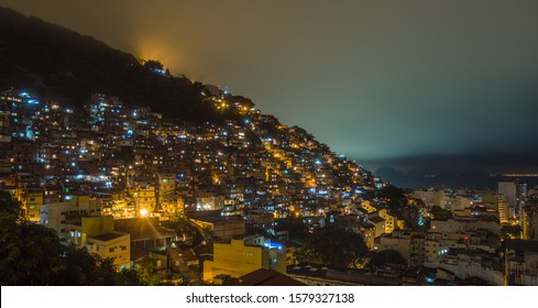 Night over Brazilian favelas on the hill with city downtown below, Rio De Janeiro, Brazil