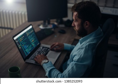The night owls in networking mode. Computer programmer working at his desk.