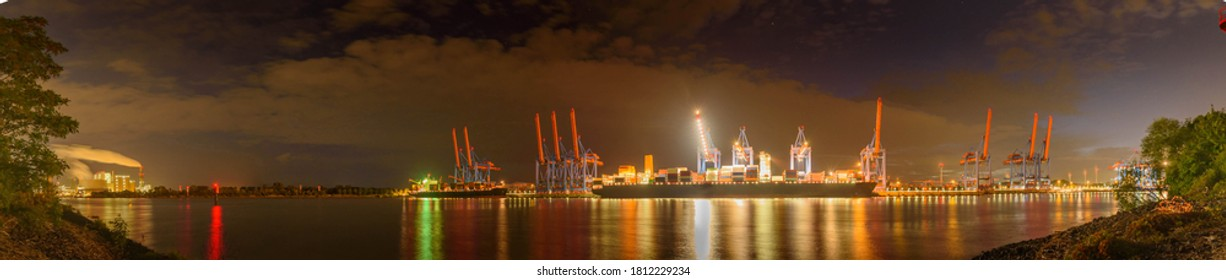 Night panorama aerial view of the container terminal in Hamburg-Altenwerder, loading and unloading of various shipping container and the Hamburg freight station.A seaport on the river Elbe in Hamburg.