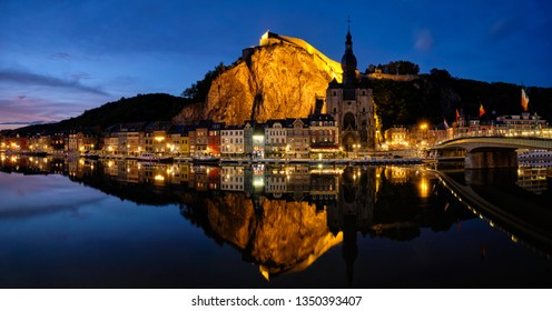 Night panorama of Dinant town, Collegiate Church of Notre Dame de Dinant over River Meuse and Pont Charles de Gaulle bridge and Dinant Citadel illuminated in the evening. Dinant,  Belgium