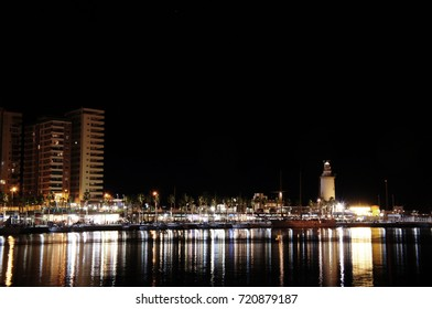 """Night panorama of the port in Malaga with """"Farola"""" lighthouse and sea reflecting the city lights"""