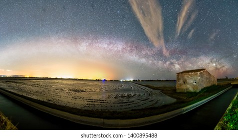 Night Panoramic Astrophotography: Milky way over   rice fields within Delta de Ebro natural park, Tarragona, Catalonia, Spain