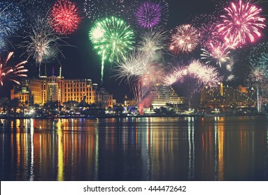 Night panoramic view of Eilat and fireworks. Red Sea coast. Israel.Seaside with water sparkle reflection.?mbankment.Hotels.Recreation and entertainment.Travel,vacation and holidays theme. Toned colors