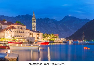 Night panoramic view of Perast old town with famous campanile of St. Nikola Church on the Bay of Kotor in Montenegro, picturesque fishing boats and yachts moorage against Dinaric Alps mountains,Europe