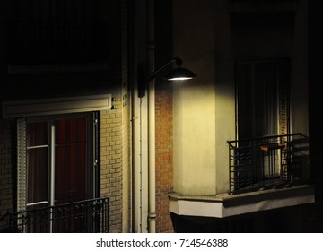 Night in Paris. A street light on a brick wall between 2 french windows