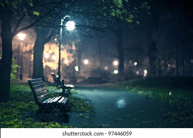 A Night in the Park. Late Autumn Night in the Park. Wood Benches and Park Alley. Horizontal Photography. Central Europe