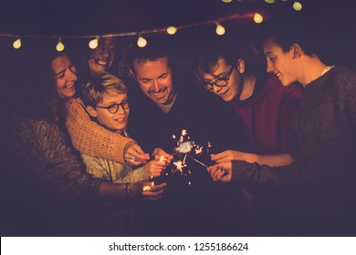 Night party celebration like new year eve 2019 or Christmas for caucasian big modern family using sparkles light fireworks together in friendship having fun - people smiling and do party