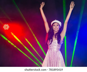 Night party,Asian teen woman to celebrate the Christmas season and Happy New Year,Happy young woman raising her arms and having fun among the colorful in night party.