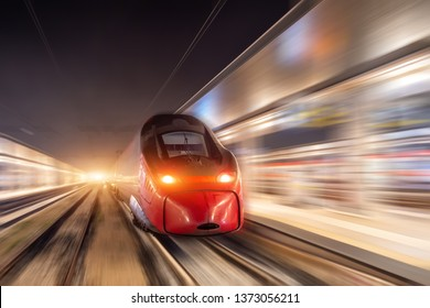 Night passenger high-speed train passing the station in the city