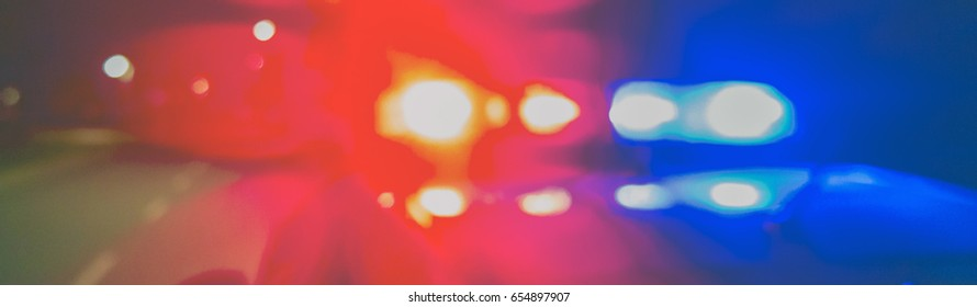 Night patrolling the city. Red and blue Lights of police car in night time. Abstract blurry image.