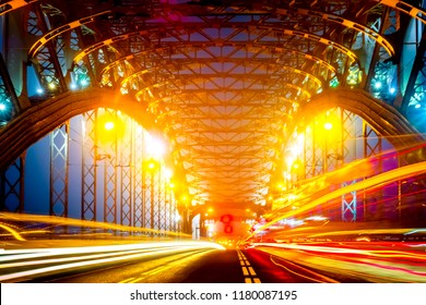 Night Petersburg. The light from the headlights of cars. Bolsheokhtinsky Bridge. Streets of St. Petersburg. Movement of cars on the bridge. Bridges of Petersburg. Russia. The Bridge of Peter the Great