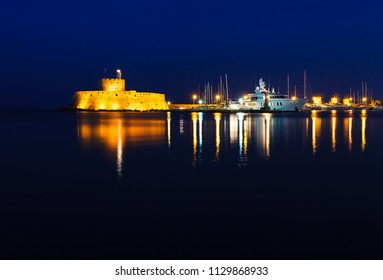 Night photo of ancient fortress and pier in Rhodes city on Rhodes island, Dodecanese, Greece. Stone walls and bright night lights. Famous tourist destination in South Europe