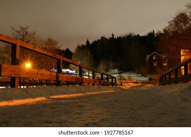 Night photo from a bridge. Wooden fence and a bright light from a lamppost. During the winter with plenty of snow. Stockholm, Sweden, Europe.