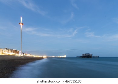 Night Photo of Brighton Skyline with old West Pier, Central Pier with fun fair lights and the new i360 attraction , Brighton, Sussex, England, UK