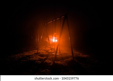 Night photo of metal swing standing outdoor at night time with fog and surreal toned light on background. Nobody there. Lonelyness concept