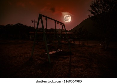 Night photo of metal swing standing outdoor at night with Moon. Nobody there. Lonelyness concept