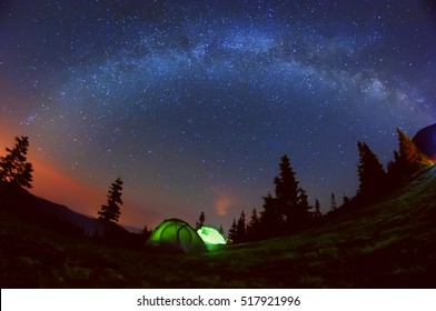 Night photo of the sky and the Milky Way. Wildlife, in a clearing in the mountains there are two glowing tent among the tall silhouettes of dark firs